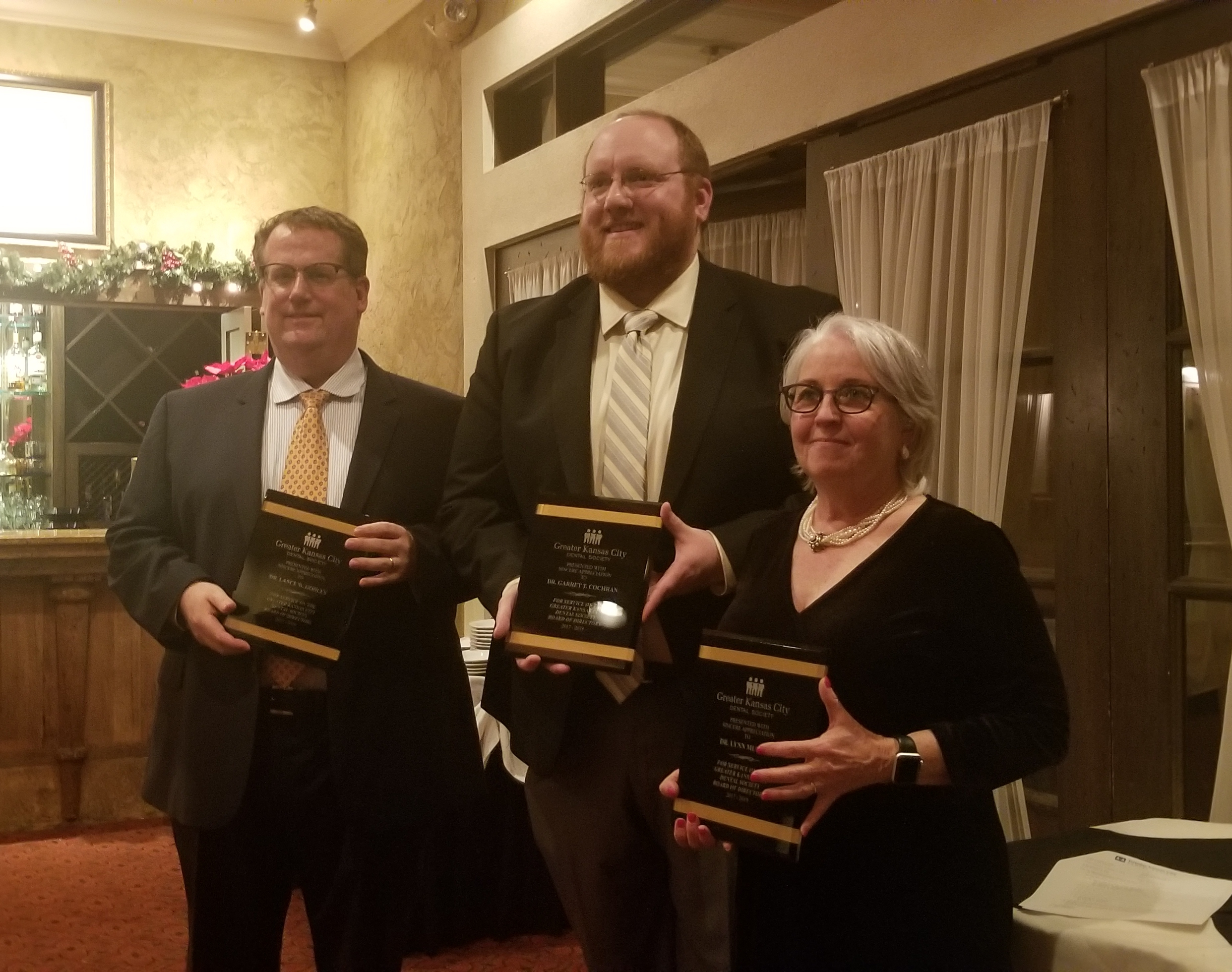 Three people with plaques